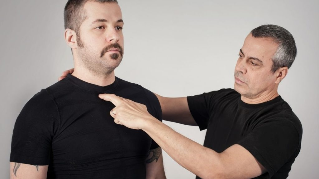 A man pointing out pressure points on another man