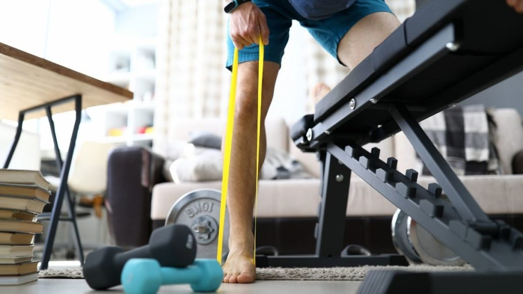 A man using exercise bands to improve muscle strength in his foot
